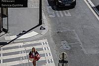 una donna con due borse rientra dalla spesa