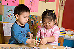 Educaton preschool  3-4 year olds fine motor literacy activity boy and girl cutting up catalogs and magazines interacting horizontal