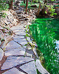 Flagstone path along Pool or Mountain Pond with waterfall.  Sylvan Pool at Ohme Gardens, a formal botanical garden in Wenatchee, Washington representative of a mountain meadow or natural park terrain with native Northwest wildflowers, flor and surprisingly fauna.  Chelan County owned.  Clear mountain pond.
