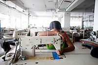 A woman worker of Tuba garments takes a rest on her sewing machine inside the factory. Dhaka, Bangladesh
