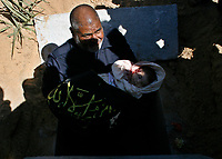 """A man carry the body of a newborn Palestinian baby, whom Palestinian medics said was killed by the Israeli forces gunfire late on Tuesday, in the central Gaza Strip March 5, 2008. Medical workers said the baby was killed and eight other people wounded by gunfire in the clash. The Israeli army said the military operation in central Gaza Strip was targeted at Palestinian militants.""""photo by Fady Adwan"""""""