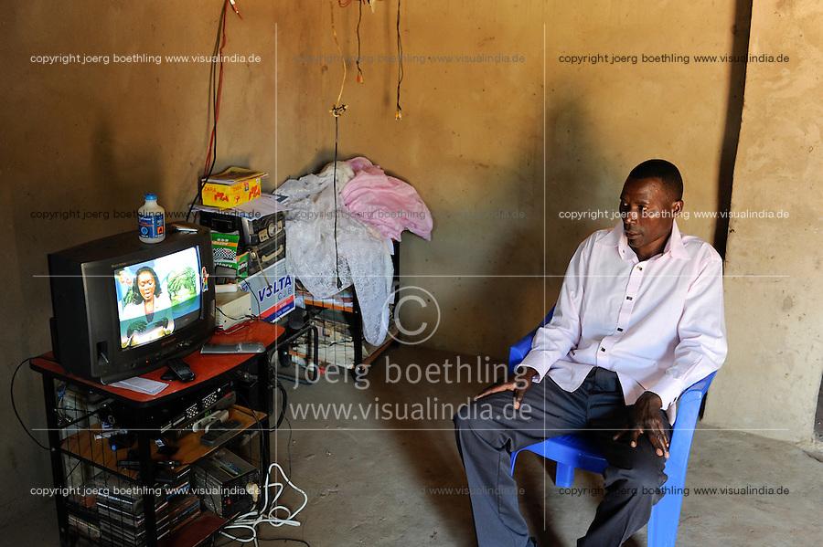 ANGOLA Kwanza Sul village Cassombo, farmer with solar powered TV / ANGOLA Kwanza Sul, Dorf Cassombo, Farmer Ernesto Arture, 38 Jahre, Fernseher mit Stromversorgung von Solarpanel auf seinem Hausdach