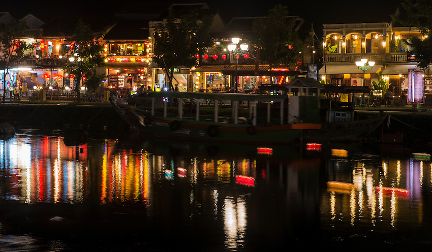 A shot across the Thu Bon River showing well lit shops at night and reflections in the river.
