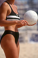A woman holds a beach volleyball about to serve during a match.