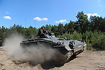 """A German tank drives around the Drawsko Pomorskie Training Area in Poland on June 10, 2015.  NATO is engaged in a multilateral training exercise """"Saber Strike,"""" the first time Poland has hosted such war games, involving the militaries of Canada, Denmark, Germany, Poland, and the United States."""