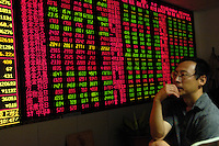 A Chinese investor watches stock index in a stock exchange of Beijing. China's bullish stock market shrugged off the central bank's most aggressive monetary tightening this year, hitting a fresh all-time high as individual investors poured money into shares..21 May 2007