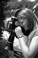 """Actress Jodie Foster, age 14, looks through eye piece of motion picture camera while appearing in the documentary film, """"Americans,"""" Los Angeles, June, 1977. Photo by John G. Zimmerman. P94427-C05-F6A."""