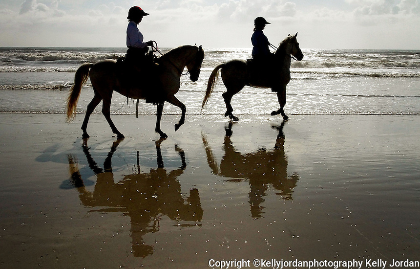 """Kelly.Jordan@jacksonville.com--042611--Pam Murphy, of Nocatee, riding Diamonte, right, and her friend Ellen O'Brien, of Palm Valley, riding Bandit head out on to the beach from Mickler's Landing for a morning of beach riding Tuesday, April 26, 2011. The riders are friends who try to ride on the beach as often as possible, the horses are PasoFino and 1/2 brothers who enjoy wading through the surf. As a beach rider for over 29 years,  Ellen says, """" riding along the ocean for an equestrian is tantamount to a golfer playing a round at Augusta National.""""(The Florida Times-Union, Kelly Jordan)"""