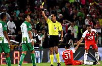 BOGOTÁ - COLOMBIA, 17-01-2019: Ferney Trujillo (Cent.), árbitro, muestra tarjeta amarilla a Brayan Rovira (Izq.), jugador de Atlético Nacional, durante partido entre Independiente Santa Fe y Atlético Nacional, por el Torneo Fox Sports 2019, jugado en el estadio Nemesio Camacho El Campin de la ciudad de Bogota. / Ferney Trujillo (C), referee, shows yellow card to Brayan Rovira (L) player of Atletico Nacional, during a match between Independiente Santa Fe and Atletico Nacional, for the Fox Sports Tournament 2019, played at the Nemesio Camacho El Campin stadium in the city of Bogota. Photo: VizzorImage / Luis Ramírez / Staff.