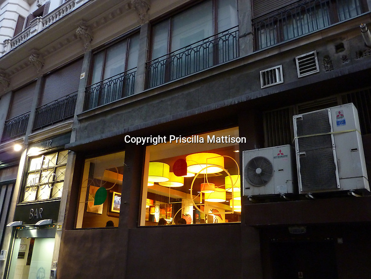 Madrid, Spain - October 15, 2011:  A brightly-lit bar contrasts with the darkened building exterior.
