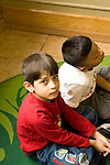 Education preschoool children ages 3-5 two boys sitting on floor one looking at camera portrait serious expression vertical