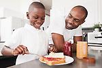USA, Metamora, Illinois, Boy (6-7) with father preparing jam sandwich