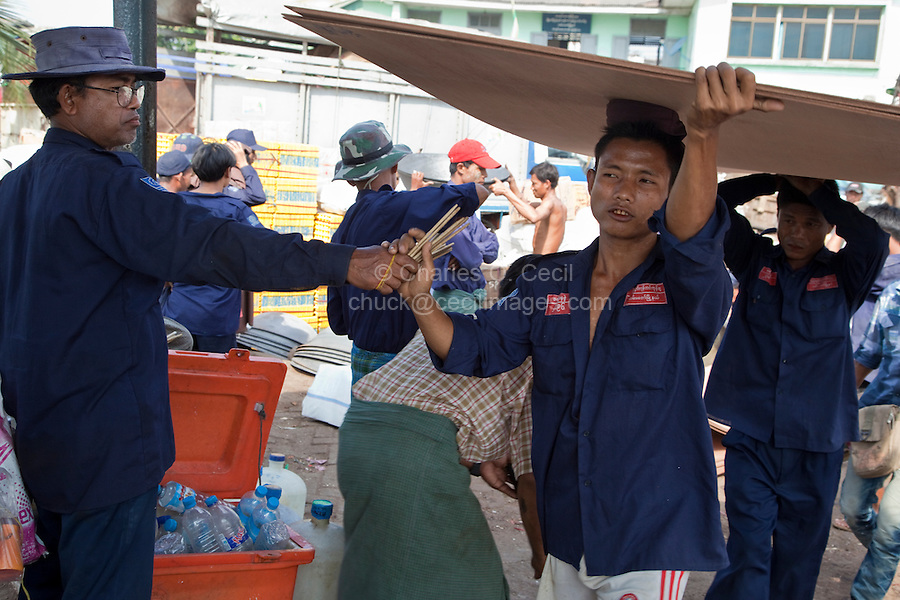 Myanmar, Burma, Yangon.  Tally Man Handing out Tally Sticks to Stevedores Carrying Plywood Sheets to Boat in Yangon River.