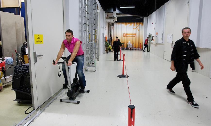 Oslo, 20091017. Skal vi danse. Carsten Skjelbreid sykler pa bakrommet i pausen for å holde kroppen i gang. svein oppmuntrer.
