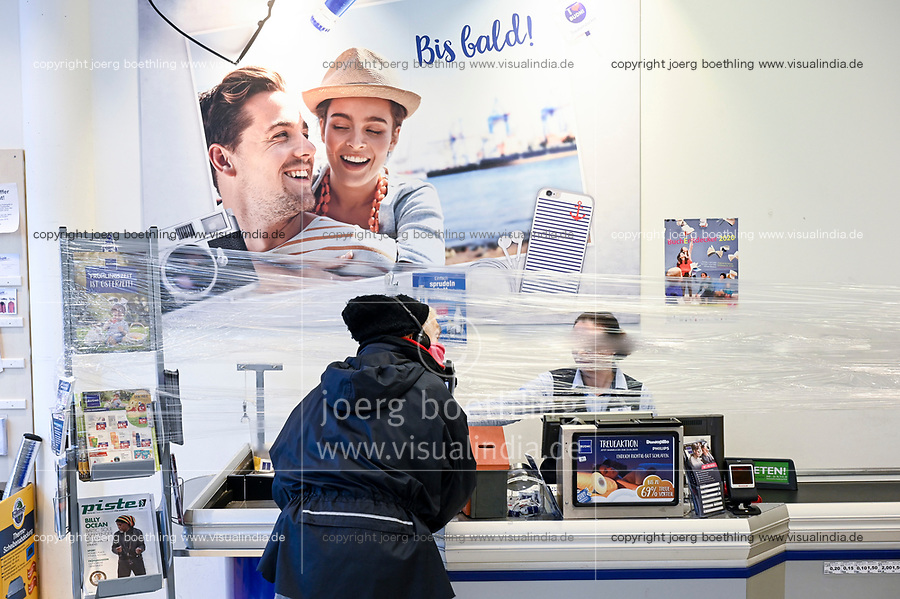 GERMANY, Hamburg, Corona Virus, COVID-19 , drugstore with protection foil for the cashier to avoid infection
