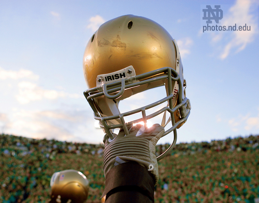 Notre Dame football players hold up their helmets in the the traditional post-game salute to the Notre Dame Stadium student section...Photo by Matt Cashore