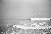France. Alpes-Maritimes department. Cannes. A lonely man stands up on a surfboard and paddles on the  Mediterranean Sea. Paddling surfboard. A paddle is a tool used for pushing against liquids as a form of propulsion.  01.11.11  © 2010 Didier Ruef