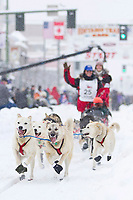 Paul Gebhart, of Kasilof, AK, waves to the cheering crowds on 4th Avenue  at the 2012 Iditarod Ceremonial Start, Anchorage, AK