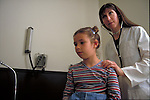 doctor examining young female patient with stethoscope