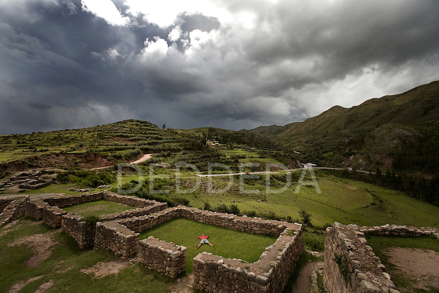 A young man meditates inside a wall of ancient Inca ruins outside Cuzco, Peru.