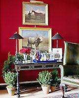 A ebonized console table with bone inlay and an 18th century wing chair in the living room.