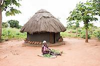 N. Uganda, Gulu District. Gwendiya village. Woman working in front of thatched hut.