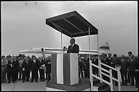 7 mai 1971. Vue de Georges Pompidou prononçant un discours à la tribune devant un groupe d'officiels, sur la piste de l'aéroport de Toulouse-Blagnac avec le Concorde derrière lui.