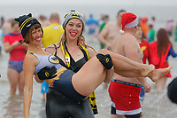 Pictured: Two women in Batman costumes. Tuesday 25 December 2018<br /> Re: Hundreds of people take part in this year's Porthcawl Christmas Swim in south Wales, UK.