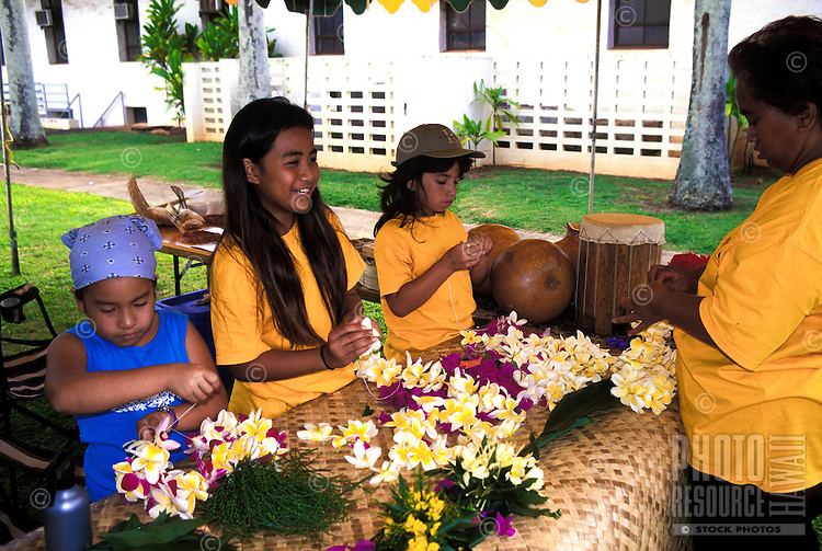 Young local hawaiian children practice the art of Lei making as part of the annual Aloha Festival. This photo taken in the town of Lehui on the island of Kauai during the aloha festivities.