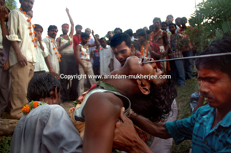 On the eve of Bengali new year an Indian man gets unconcious after piercing his tounge with an iron rod to bring good fate in the new year while viewers watch and shout with the name of lord shiva. This is a sacrifice to Lord Siva done by people staying in the rural Bengal. Another form of religious blindness in one of the fastest developing country. Medinipore near Kolkata, India. Arindam Mukherjee
