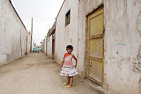 A young girl stands in a back-alley. Dunhuang, Gansu Province. China