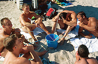 """Spain. Mallorca in the Balearic islands. Palma. German tourists (young men) drink sangria with big straws from a large blue bucket on the sandy beach of the """" Playa de Palma"""" in front of the Balneario 6. © 1999 Didier Ruef"""