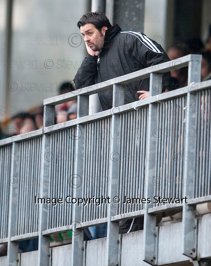 An unhappy looking Alloa Manager Paul Hartley looks on from the stand as he starts his dug out ban.