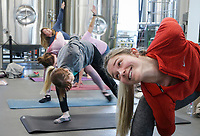 Karson Stone (right) performs a yoga movement, Saturday, February 13, 2021 at the Bentonville Brewing Company in Bentonville. The brewhaus hosted a free yoga class inside the brewery due to the cold weather. Check out nwaonline.com/210213Daily/ for today's photo gallery. <br /> (NWA Democrat-Gazette/Charlie Kaijo)