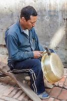 Bhaktapur, Nepal.  Metalworker Hammering a Pot into Shape.