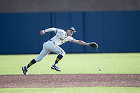 Michigan Wolverines shortstop Benjamin Sems (2) reaches for a grounder against the Michigan State Spartans on March 21, 2021 in NCAA baseball action at Ray Fisher Stadium in Ann Arbor, Michigan. Michigan scored 8 runs in the bottom of the ninth inning to defeat the Spartans 8-7. (Andrew Woolley/Four Seam Images)