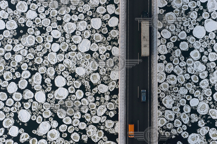 A lorry and cars travel on a road past the ice covered Vistula River near the village of Kiezmark.