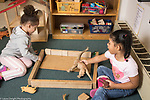 Education Preschool 3-4 year olds two girls building an enclosure for dinosaur toys from wooden blocks