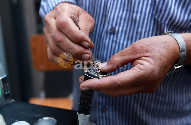 Palestinian watchmaker Haider Mahmoud, 63, fixes mechanical watches at al-Zawya market, in Gaza City on August 9, 2021. Mahmoud has been working as a watchmaker since 50 year, after securing it on behalf of his father. A mechanical watch is a watch that uses a clockwork mechanism to measure the passage of time, as opposed to quartz watches which function electronically via a small battery, or radio watches. Photo by Omar Ashtawy