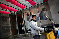 CHINA. Shanghai. A street cleaner outside of a fashion store. Shanghai is a sprawling metropolis or 15 million people situated in south-east China. It is regarded as the country's showcase in development and modernity in modern China. This rapid development and modernization, never seen before on such a scale has however spawned countless environmental and social problems. 2008
