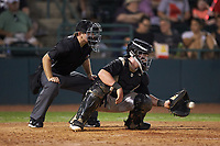 Kannapolis Intimidators catcher Evan Skoug (11) receives a pitch as home plate umpire Brandon Blome looks on during the game against the Hickory Crawdads at L.P. Frans Stadium on July 20, 2018 in Hickory, North Carolina. The Crawdads defeated the Intimidators 4-1. (Brian Westerholt/Four Seam Images)