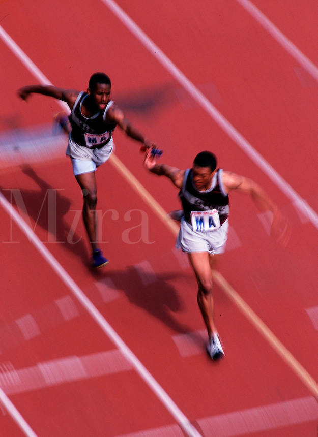 Overhead view of male runners passing off the baton at a track meet.