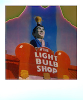 """In this instant-film image shot on expired Polaroid 600 film, a light bulbs-only specialty store is topped by a smartly dressed man with a classic """"IDEA"""" light bulb over his head - Stock Image."""