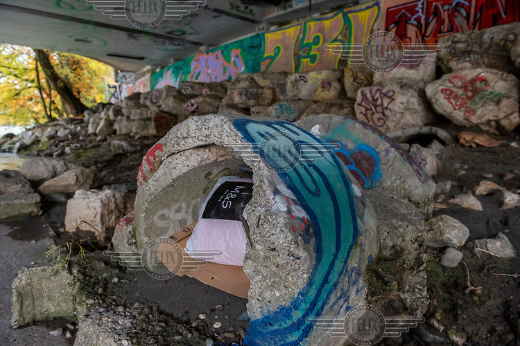 A homeless person's belongings hidden in an old concrete culvert beneath the Pont des Acasias beside the Arve River.