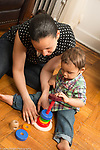 18 month old toddler boy at home with mother playing with stacking toy, helped and supported by her, steadying toy
