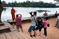 Bizarre - Tourists taken photos of a Buddhist Monk against the background of  Angkor Wat, Cambodia