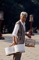 China, Peking, beim Himmelstempel (Tian Tan), Mann mit Vogelkäfigen