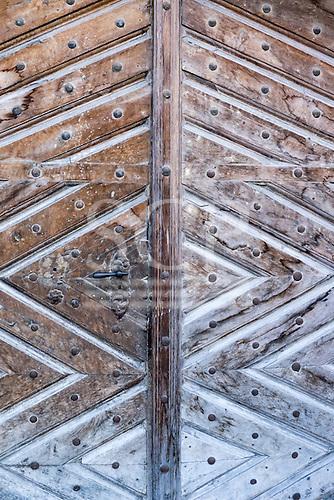 Switzerland. Traditional old style wooden door with geometric design and metal door handle.