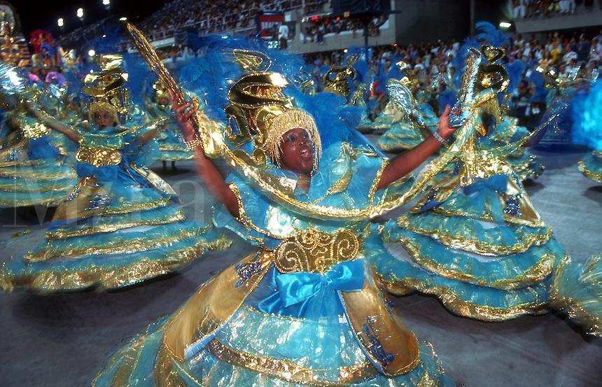 Carnivale dancers in ornate costumes dance the Samba. Rio De Janeiro, Brazil.