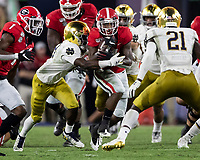 ATHENS, GA - SEPTEMBER 21: D'Andre Swift #7 of the Georgia Bulldogs is tackled by TaRiq Bracy #28 of the Notre Dame Fighting Irish during a game between Notre Dame Fighting Irish and University of Georgia Bulldogs at Sanford Stadium on September 21, 2019 in Athens, Georgia.